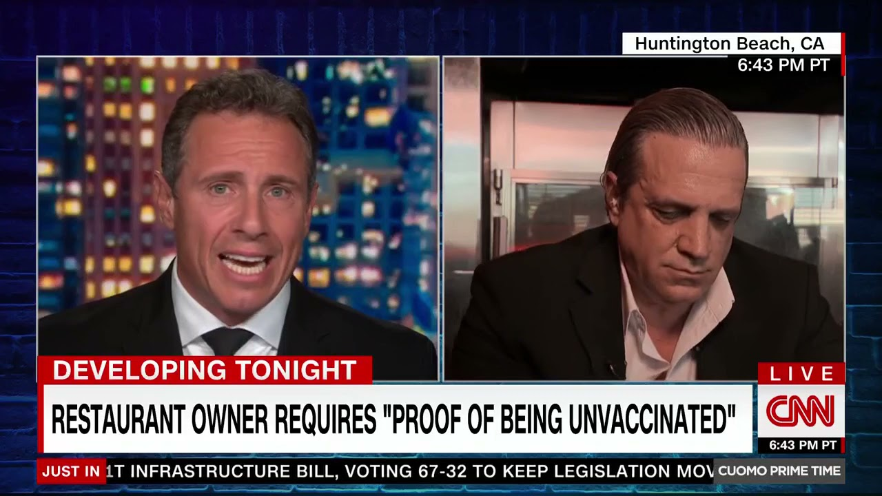 """Chris Cuomo interviews a restaurant owner above a chyron reading """"restaurant owner requires 'proof of being unvaccinated'"""""""