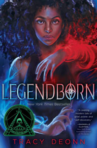 """""""Legendborn"""" by Tracy Deonn featuring a Black teenager with voluminous black hair moving red and blue clouds of magic."""
