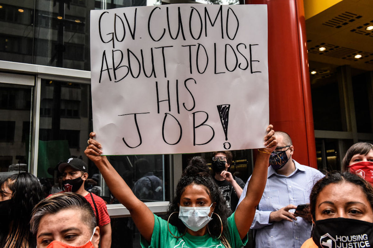 """A protester wearing a mask holds a sign reading """"Gov. Cuomo about to lost his job!"""""""