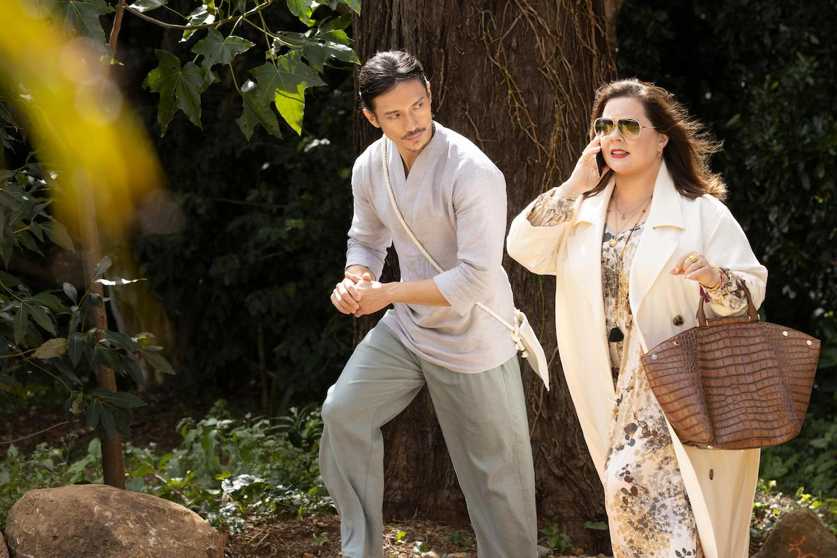 Yao (Manny Jacinto) and Frances (Melissa McCarthy), talking on her cell phone, walk outdoors in a scene from Nine Perfect Strangers.