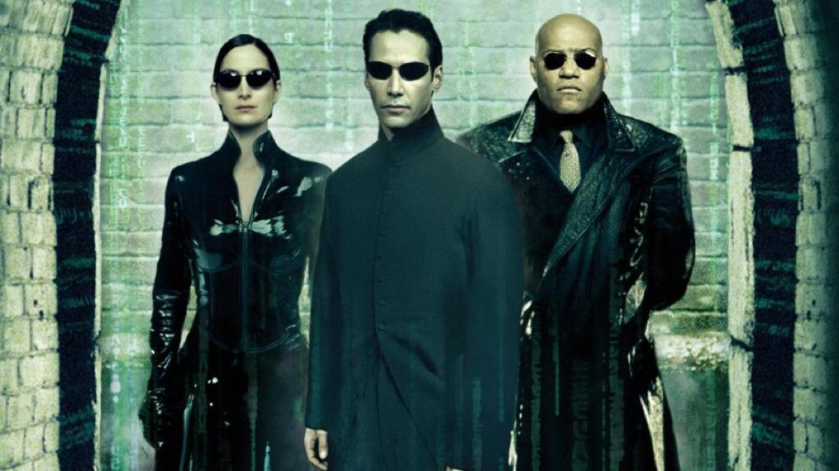 Neo (Keanu Reeves), Trinity (Carrie-Anne Moss), and Morpheus (Laurence Fisburne) standing together and staring into the camera in dark sunglasses in The Matrix Reloaded poster.