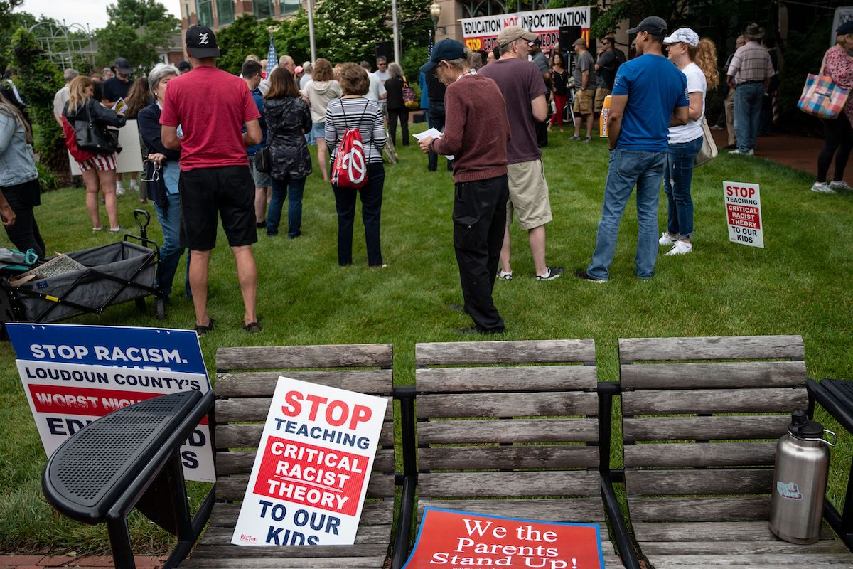 """Signs are seen on a bench during a rally against """"critical race theory"""" (CRT) being taught in schools"""