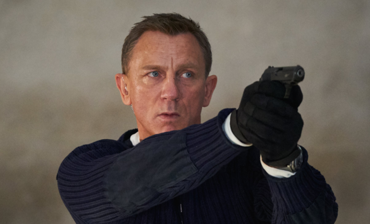 Daniel Craig holds a gun with both hands as James Bond in 'No Time to Die'